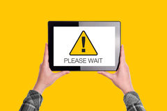 Please Wait Message on Digital Tablet Computer Display. Woman Holding Device, Isolated on Yellow Background Stock Photography