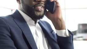 Pleased African-American man in suit talking on cellphone, making an appointment