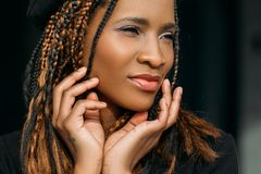 Pleased African American young woman. Seductive pretty female on dark background, stylish haircut, happiness concept stock photos