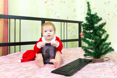 Pleased baby in new year suit with tablet computer Royalty Free Stock Photo