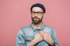 Pleased bearded man with closed eyes, keeps hands on chest, dressed in fashionable clothes, isolated over pink studio background. royalty free stock photo