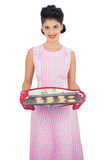Pleased black hair model holding a baking tray of cookies Stock Photo