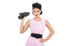 Pleased black hair model holding binoculars Stock Images