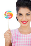 Pleased black hair model holding a colored lollipop Royalty Free Stock Photo