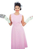 Pleased black hair model holding a pan and wearing rubber gloves Stock Photos
