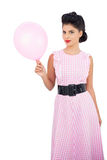 Pleased black hair model holding a pink balloon Royalty Free Stock Photo
