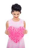 Pleased black hair model holding a pink heart shaped pillow Stock Photo