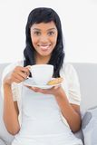 Pleased black haired woman in white clothes drinking coffee Royalty Free Stock Image