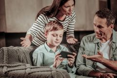 Pleased blonde boy being infatuated with his game. I do not like it. Worried women talking to her husband and pointing at her son royalty free stock photography