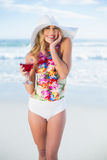 Pleased blonde model in swimsuit holding a cocktail Stock Image
