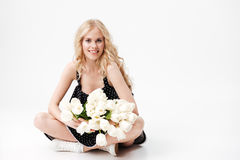 Pleased Blonde woman sitting on floor with bouquet of flowers Royalty Free Stock Images