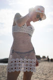 Pleased blonde woman in white beach dress Stock Image