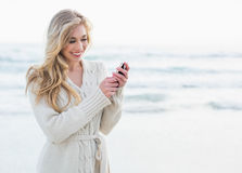 Pleased blonde woman in wool cardigan using a mobile phone Stock Images
