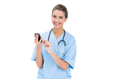 Pleased brown haired nurse in blue scrubs using a mobile phone Stock Image