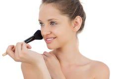 Pleased brunette model applying powder on her cheek Stock Images