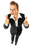 Pleased business woman showing thumbs up gesture Stock Images