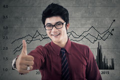 Pleased businessman with financial statistics Stock Photography