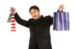 Pleased businessman holding shopping bags in hands Royalty Free Stock Photography