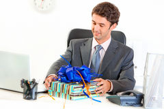 Pleased businessman in office looking on gift Stock Images