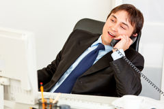 Pleased businessman in office talking on phone Royalty Free Stock Image