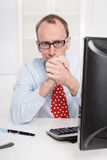 Pleased businessman sitting at desk clasping Hands. Stock Photo