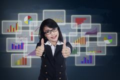 Pleased businesswoman giving thumbs up Stock Photography