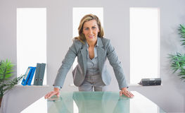 Pleased businesswoman standing in front of a desk Stock Photo
