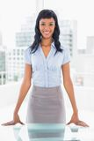 Pleased businesswoman standing at her desk Stock Images