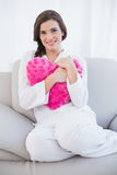 Pleased casual brown haired woman in white pajamas cuddling a heart shaped pillow Stock Photos