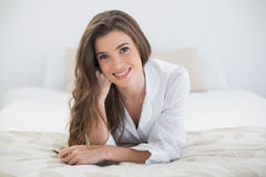 Pleased casual brown haired woman in white pajamas lying on her bed Royalty Free Stock Photos