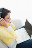 Pleased casual brunette in yellow cardigan listening to music while using a laptop Royalty Free Stock Image