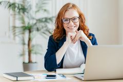Pleased cheerful red haird female economist develops financial startup project, poses in office interior, works in business sphere stock photos