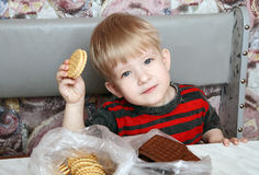 Pleased with the child with cookies in hand Stock Photo