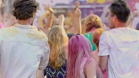 Pleased crowd colored with powder paint dancing at open-air concert, Holi fest. Stock footage stock video