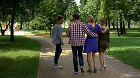 Pleased family members walking in park, enjoying perfect weekend together royalty free stock images