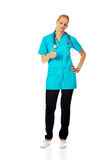 Pleased female doctor or nurse showing thumb up Stock Image