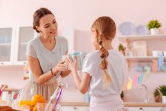 Pleased female person communicating with her kid. Being thankful. Delighted young women expressing positivity while taking gift box stock photos