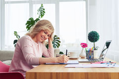 Pleased female with pretty smile writing in notebook while sitti Royalty Free Stock Images
