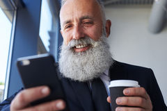 Pleased gentleman age of 50-60 holding cup of coffee and surfing Stock Photos