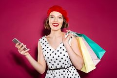 Pleased ginger woman in dress holding packages and smartphone. While looking at the camera over pink background stock photo
