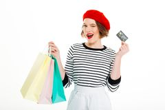 Pleased ginger woman with packages holding credit card. And winks at the camera over grey background royalty free stock photos