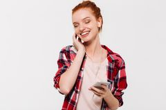Pleased ginger woman in shirt and headphones listening music stock image