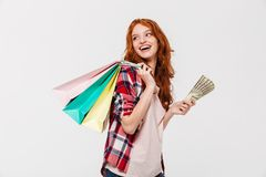 Pleased ginger woman in shirt holding packages on shoulder. With money in hand while looking back over gray background stock photo
