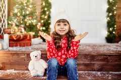 Pleased girl claps her hands sitting on the porch Royalty Free Stock Photography