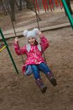 Pleased girl on a swing. In cold weather Stock Photo