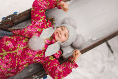 Pleased girl on a winter sliding board Royalty Free Stock Image