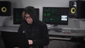 Pleased Hacker in a black hoodie with color kayushonom sitting at his natbukom and engaged in hacking programs. In the stock footage