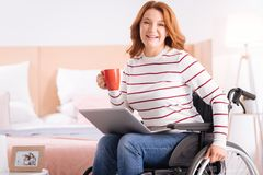 Pleased handicapped woman having coffee Stock Photo