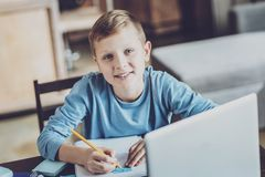 Pleased kid doing home task with pleasure royalty free stock photo