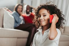 Pleased kid using cellphone in living room Royalty Free Stock Photography